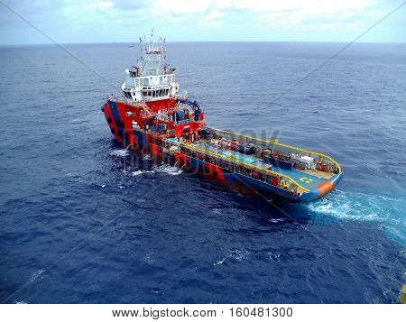 Supply boat transfer cargo to oil and gas industry and moving cargo from the boat to the platform, boat waiting transfer cargo and crews between oil and gas platform with the boat.