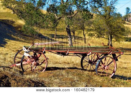 Rustic wooden wagon at a rural field surrounded by Oak Trees taken on a ranch in the Western Sierra Nevada Mountains Foothills, CA