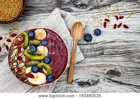 Acai breakfast superfoods smoothies bowl with chia seeds bee pollen goji berry toppings and fruits. Overhead top view flat lay copy space