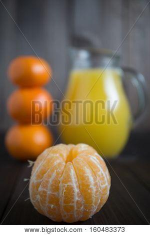 peeled tangerine mandarine with jug of fresh juice and few tangerines as blurred background