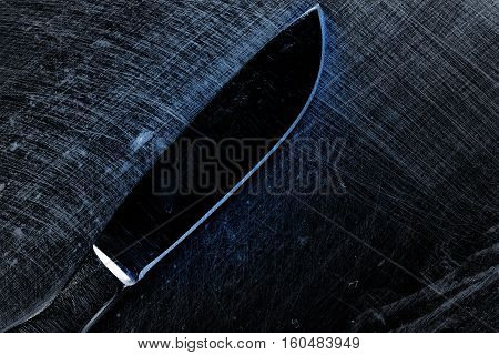 Scalpel on the scraped metal surface. Metallic background