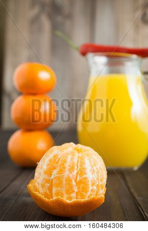 peeled tangerine mandarine with jug of fresh juice pepper chili on top and few tangerines as blurred background