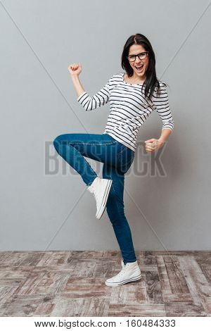 Image of happy young woman wearing eyeglasses make winner gesture over grey background. Look at camera.