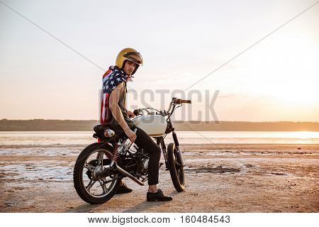 Young brutal man in golden helmet and american flag cape sitting on his motocycle holding water bottle
