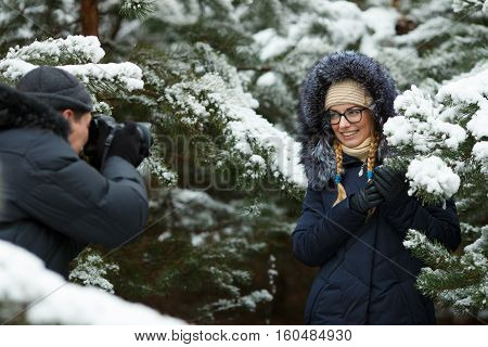 Young adorable blond woman in glasses wearing blue hooded coat having photoshooting in snowy winter forest outdoors. Outdoors photography cold season freshness concept.