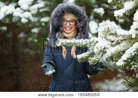 Young Adorable Blond Woman In Glasses Wearing Blue Hooded Coat Having Fun In Snowy Winter Forest Out
