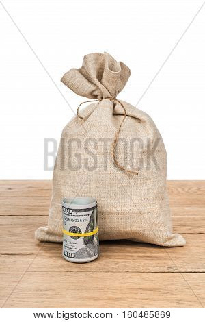 Big bag of money tied and twisted roll of dollars tied with yellow rubber band on the old wooden table isolated on white background