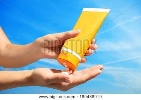 Female hands with sun protection cream on sky background. Skin care concept.