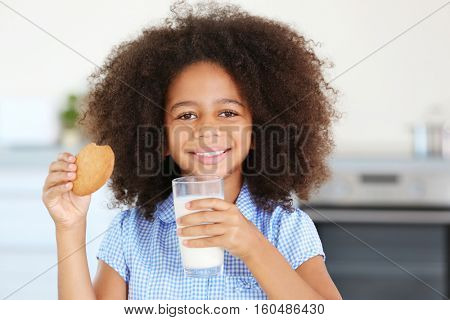 Pretty African-American girl preferring to drink milk with cookies