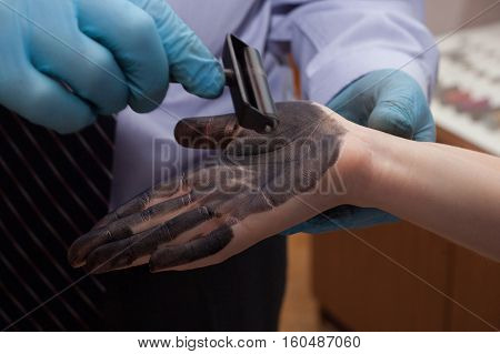 The investigation of the crime. The inspector takes fingerprints of a suspect.