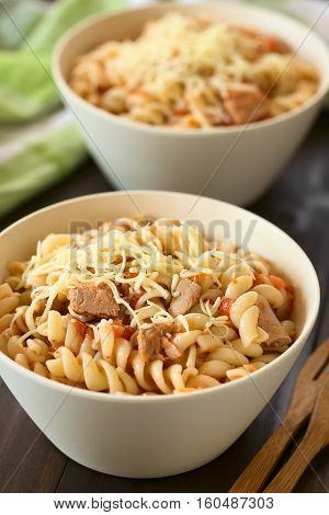 Rotini pasta with tuna and tomato sauce and grated cheese on top photographed with natural light (Selective Focus Focus in the middle of the first dish)