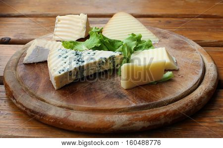 Various slices of cheese on a traditional round wooden plate.
