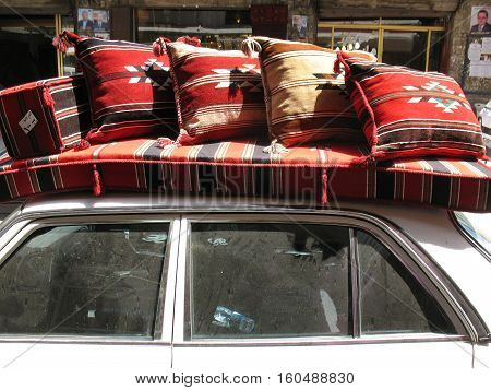 A scene from a Lebanese old souk in the city of Tripoli. A car transporting furniture on its top.