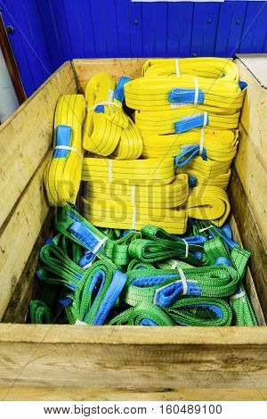 Nylon soft lifting slings stacked in a wooden box. Warehouse of finished products for industrial enterprises