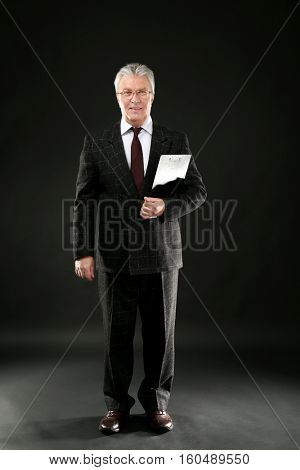 Senior businessman with clipboard on black background