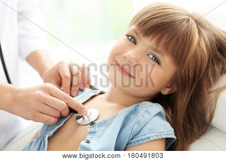 Pediatrician examining little girl's heart