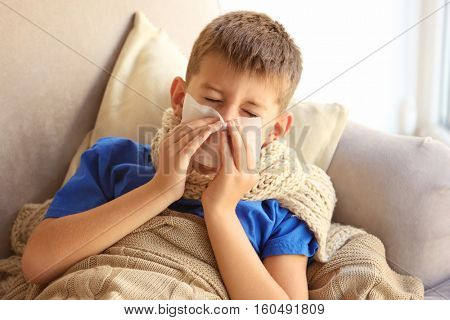 Small sick boy blowing his nose in bed