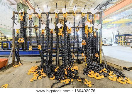 Warehouse of finished products of the enterprise for the production of handling removable devices. Rack with new cargo chain slings.