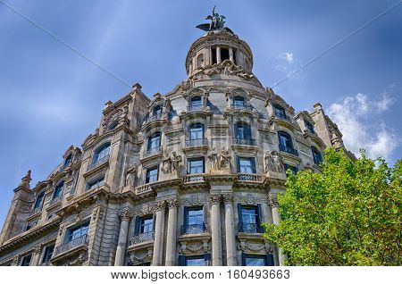 Interesting facade with statues on blue sky background in Barcelona, summer Spain