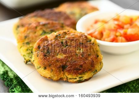 Zucchini couscous and parsley fritters with tomato and onion dip on the side photographed with natural light (Selective Focus Focus in the middle of the first fritter)