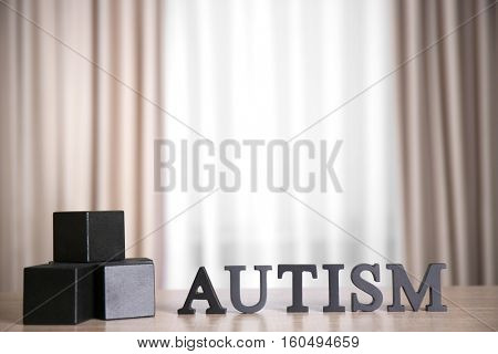 Wooden cubes on curtains background. Autism concept