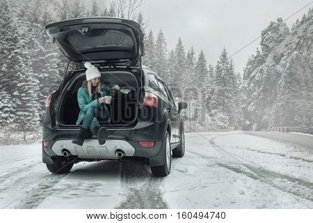 Woman at winter time. Young female with hot tea in her hands sitting in black car at snowy winter day.