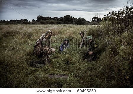 Hunting scene with group of hunters in rural field with dramatic sky in expectation of hunting in tall grass during hunting season