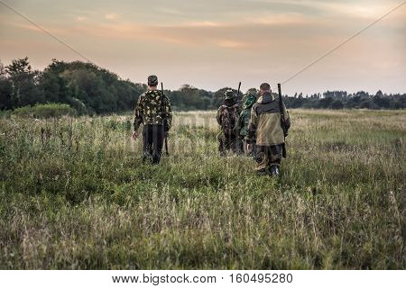 Hunting scene with hunters going through rural field during hunting season in overcast day during sunset with moody sky