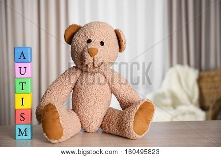 Colorful wooden cubes with Teddy bear on curtains background. Autism concept