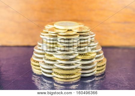 The pyramids of gold and silver coins on brown blurred background. Business concept growth Finance.