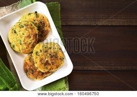 Zucchini couscous and parsley fritters photographed overhead with natural light (Selective Focus Focus on the top of the fritters)