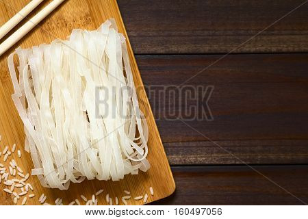 Raw rice flour noodles on wooden board photographed overhead on dark wood with natural light (Selective Focus Focus on the top of the noodles)