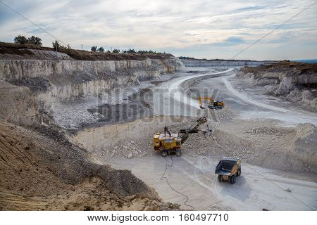 Excavators and dump trucks working and extracting the chalk in a quarry