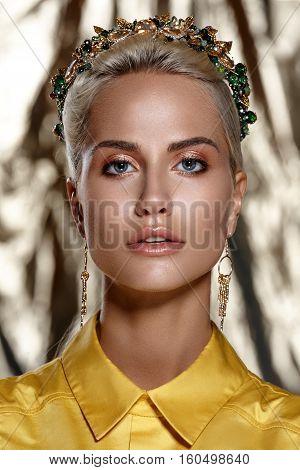 fashion studio photo of beautiful blonde woman with bright makeup wearing crown in hairand yellow shirt