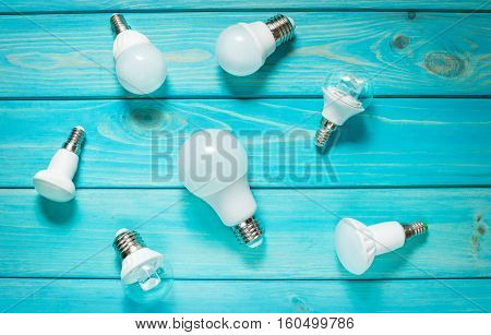 Set of different row LED bulbs on blue wood background