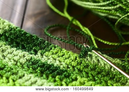 Crochet handicraft making a place mat out of green yarn with a pattern of double stitches using a metal crochet hook or needle photographed with natural light (Selective Focus Focus on the hook of the needle)
