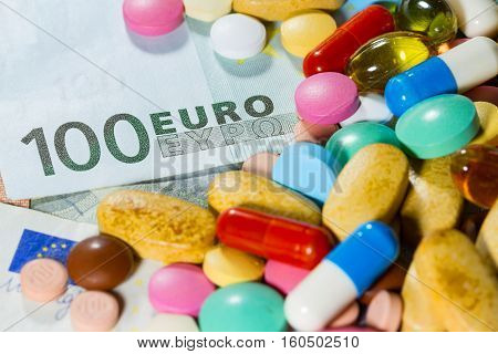 Euro banknotes with medical instruments and different color pills