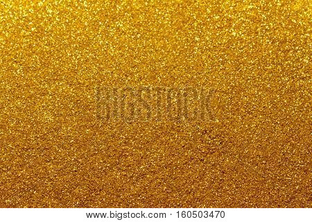 Abstract gold colored glitter background with shining light and soft bokeh, festive colors