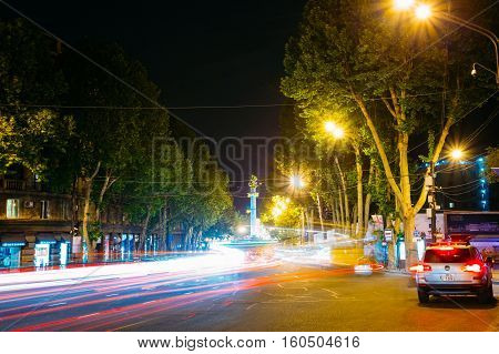 Tbilisi, Georgia - May 20, 2016: Night View Of The Liberty Monument And Rustaveli Avenue In Bright Illumination With White And Red Motion Blur Effect On The Road In Summer Under Black Sky.