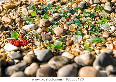 Green pieces of glass on the beach, polished by the sea. Pebble Beach. Seashells and ocean rocks. Marine background.