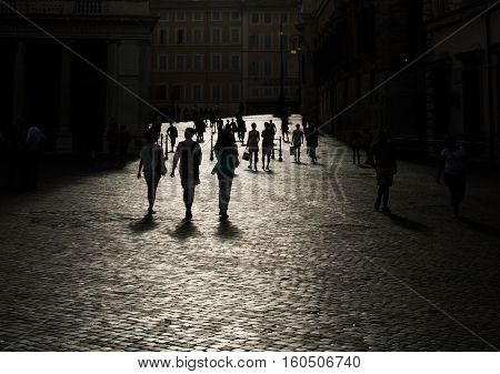 Black silhouettes on bright lighted cobble-stone pavement Rome Italy