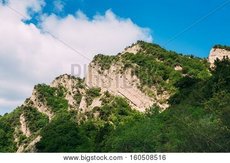 Mtskheta, Georgia. The View Of White Limestone Mountaintop Overgrown With Dense Green Vegetation In The Area Of Shiomgvime Or Shio-Mgvime Monastery In Sunny Spring Under Blue Cloudy Sky.