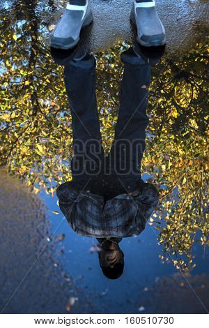 Reflection in a puddle of man framed by autumn leaves on a tree