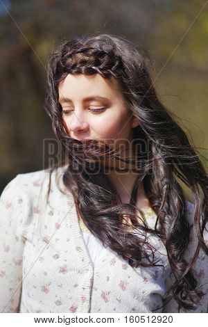 Portrait is incredibly beautiful long haired brunette girl with drooping lashes the wind ruffling her silky curls closeup on blurred background