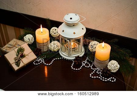 Christmas decoration big candles white balls and presents pacing at paper on wooden table in cafe.