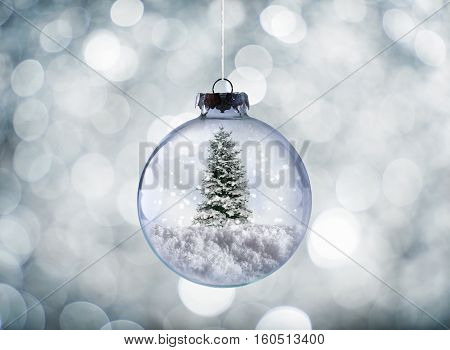 Crystal Christmas ball with xmas tree on snow and sparkling silver background