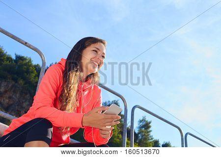 Woman Sitting With Phone On The Tribune Stadium .
