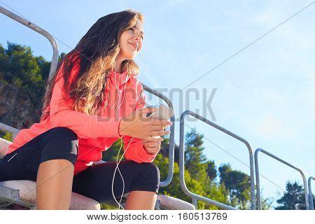 Woman Listens To Music On Phone On The Tribune Stadium .