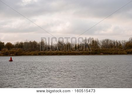 River Bank forest and rippled water surface with river beaconon foreground in bad weather day.