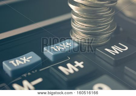 stack of coins on calculator near tax signconcept for business and tax time.